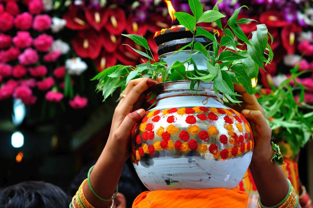"""A woman carries the """"Ghatam"""", a pot beautifully decorated with turmeric, vermilion, flowers, and neem leaves; with an oil lamp at the top. The pot contains the """"Bonam"""", the food offered to the Goddess."""