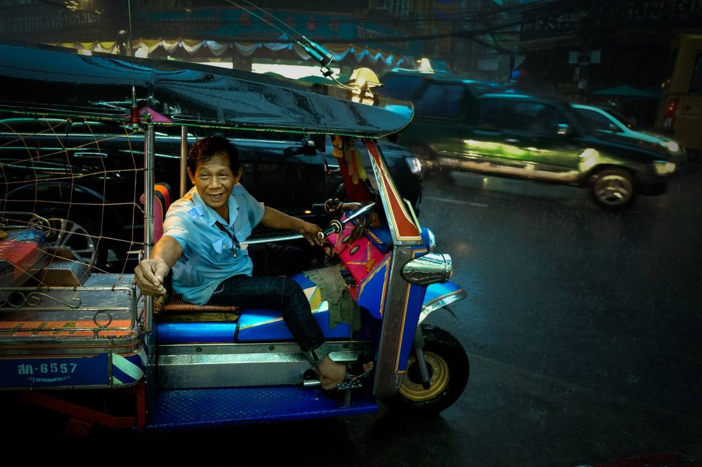 A tuktuk driver exchanges the fare in a heavy rain