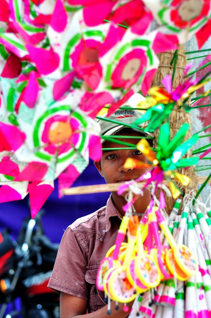 A kid selling paper-windmills during the 2nd day of Bonalu celebration.