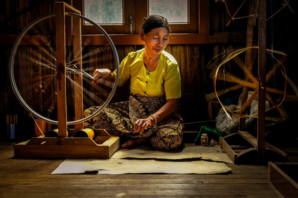 A lady spins threads extracted from lotus stems