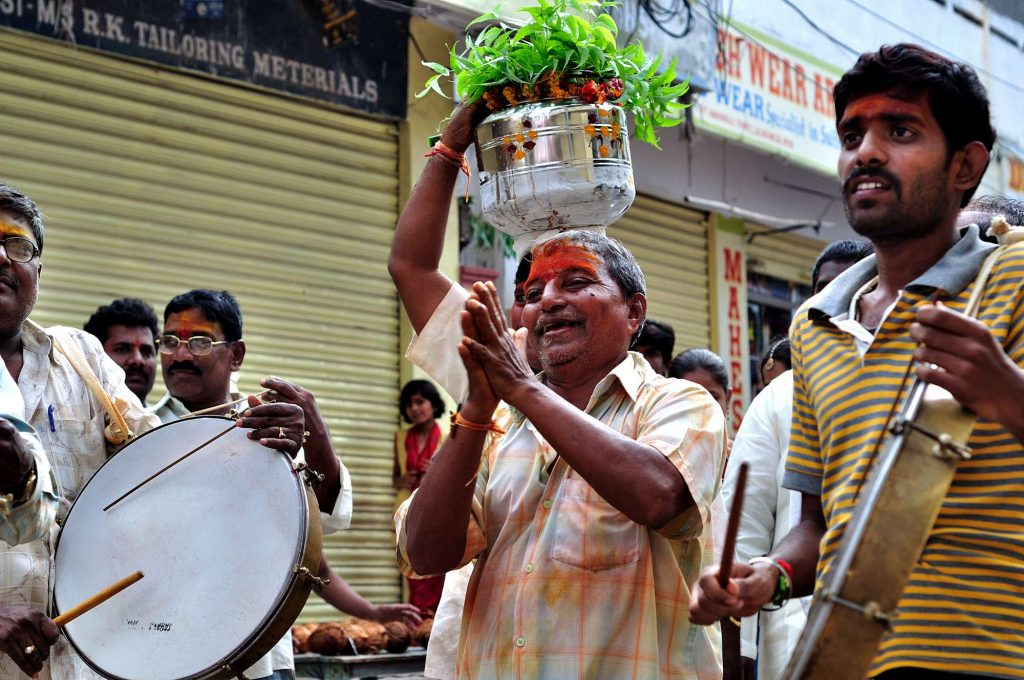 A man is seen dancing as the procession moves towards the temple.