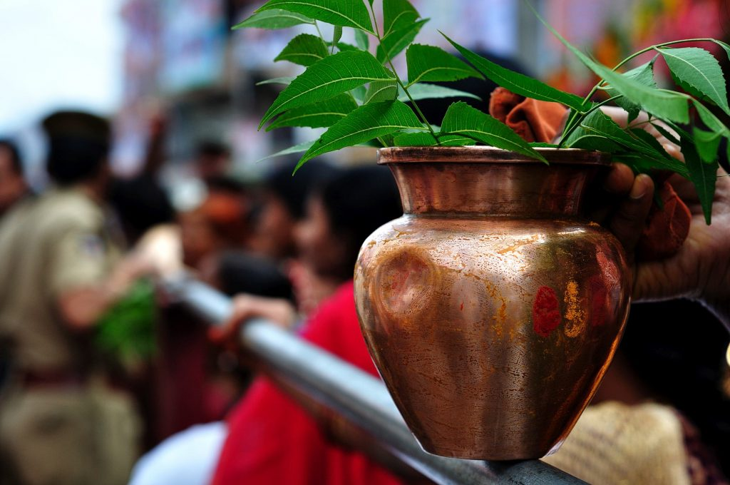 A lady rests her pot on the railing as she waits in the queue before entering into the temple.