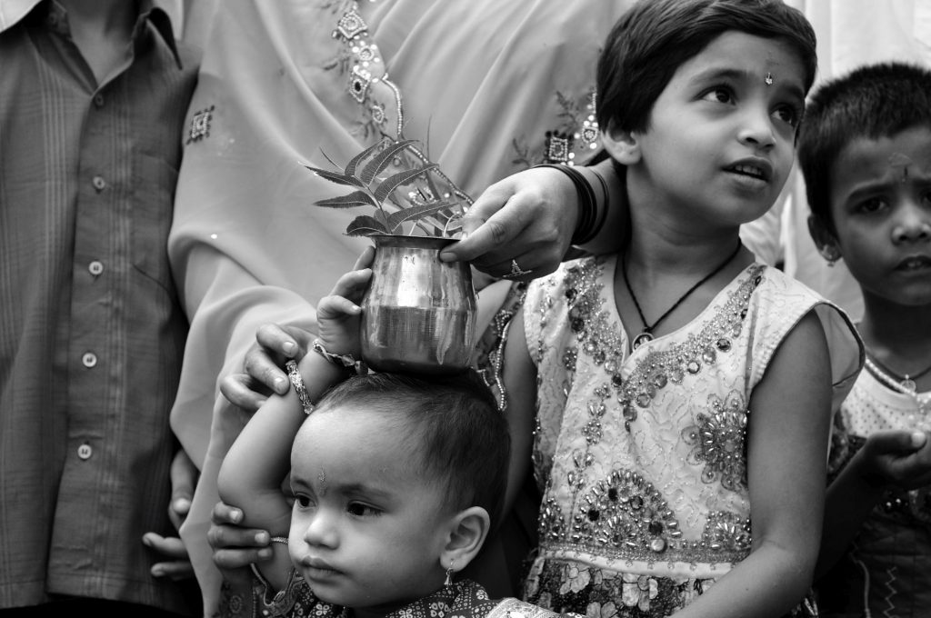 A mother helps her kid as she tries to carry a metal pot on her head.