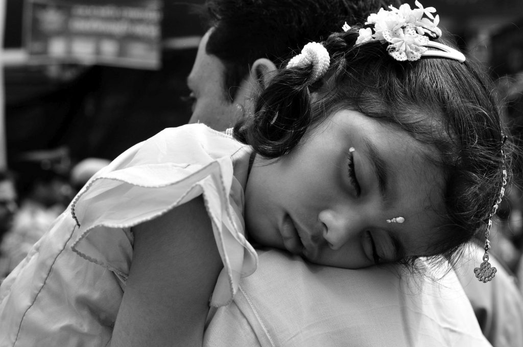 A kid sleeps on the shoulder of her father as they wait for her mother outside the temple.