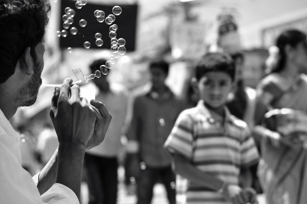 A kid passes by while a vendor blows soap bubbles to attract customers on the 2nd Sunday of the Bonalu festival.