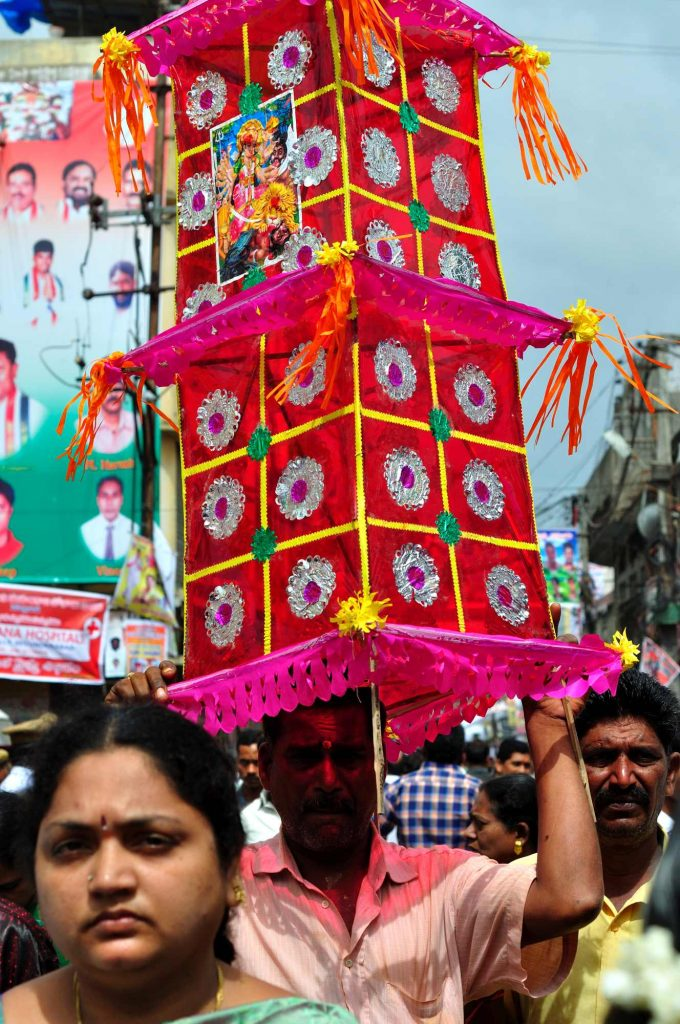 """A person is carrying """"Thottela"""" (a small colorful, paper structure supported by sticks), which is marked as respect and offered to the Goddess by a group of devotees."""