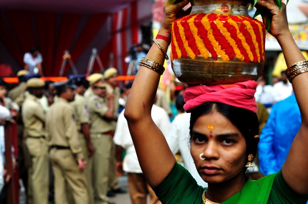 Polices are seen as a devotee carries her offering. The police and RAF (Rapid Action Force) are delegated to maintain the crowd and to avoid any unwanted commotion during the festival.
