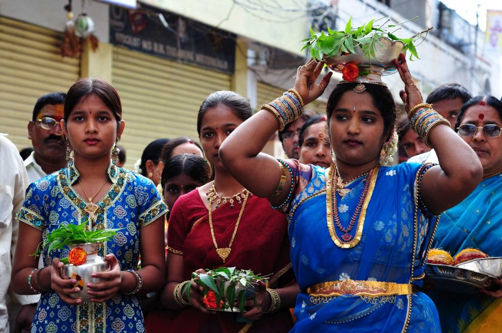 Girls and women, dressed in beautiful sarees and jewelries, walk along with the procession to the temple.