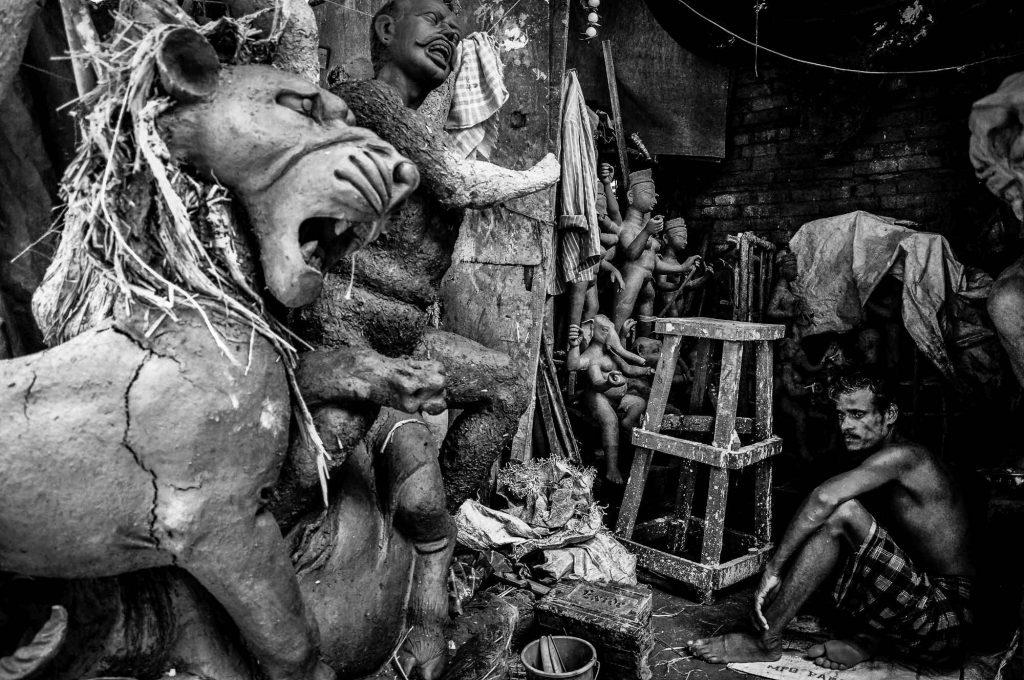 An artisan contemplates amidst the idols