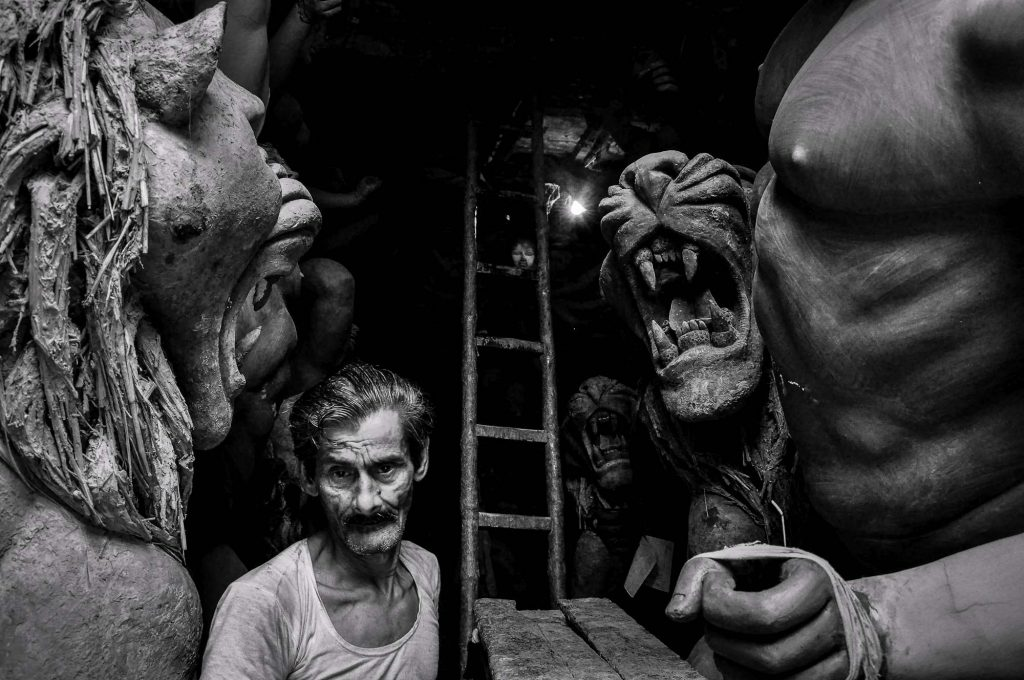 A man walks in between the idols in one of the workshops at Kumartuli