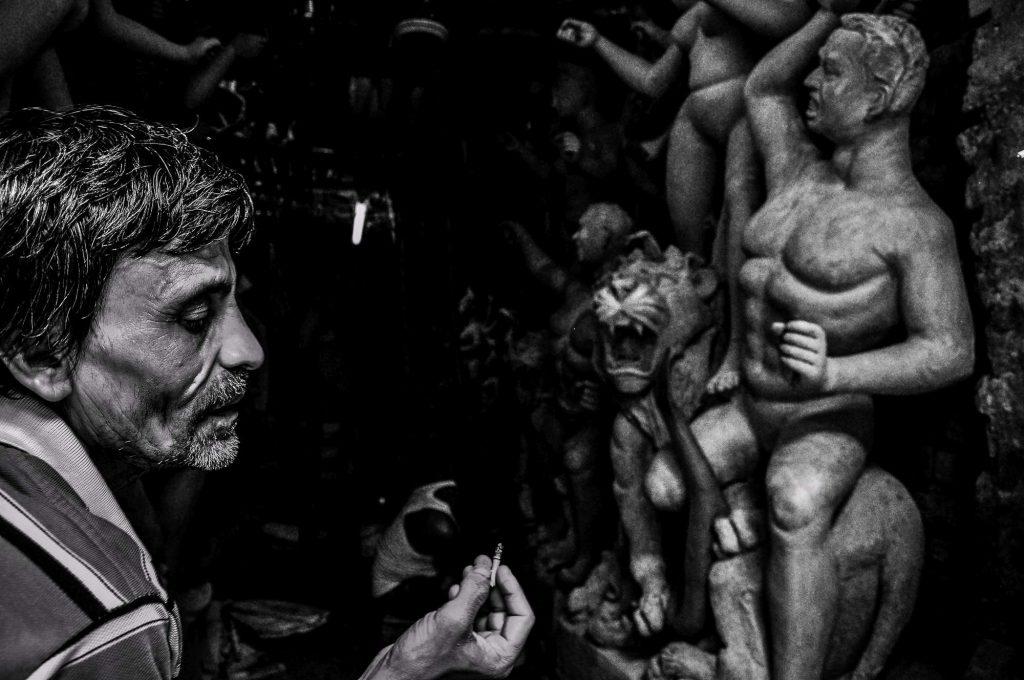 A man smokes outside his studio