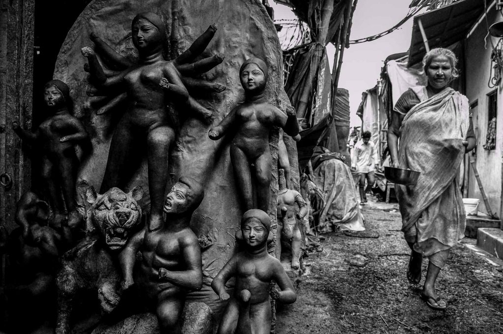 An old lady passes by the idols in the streets of Kumartuli