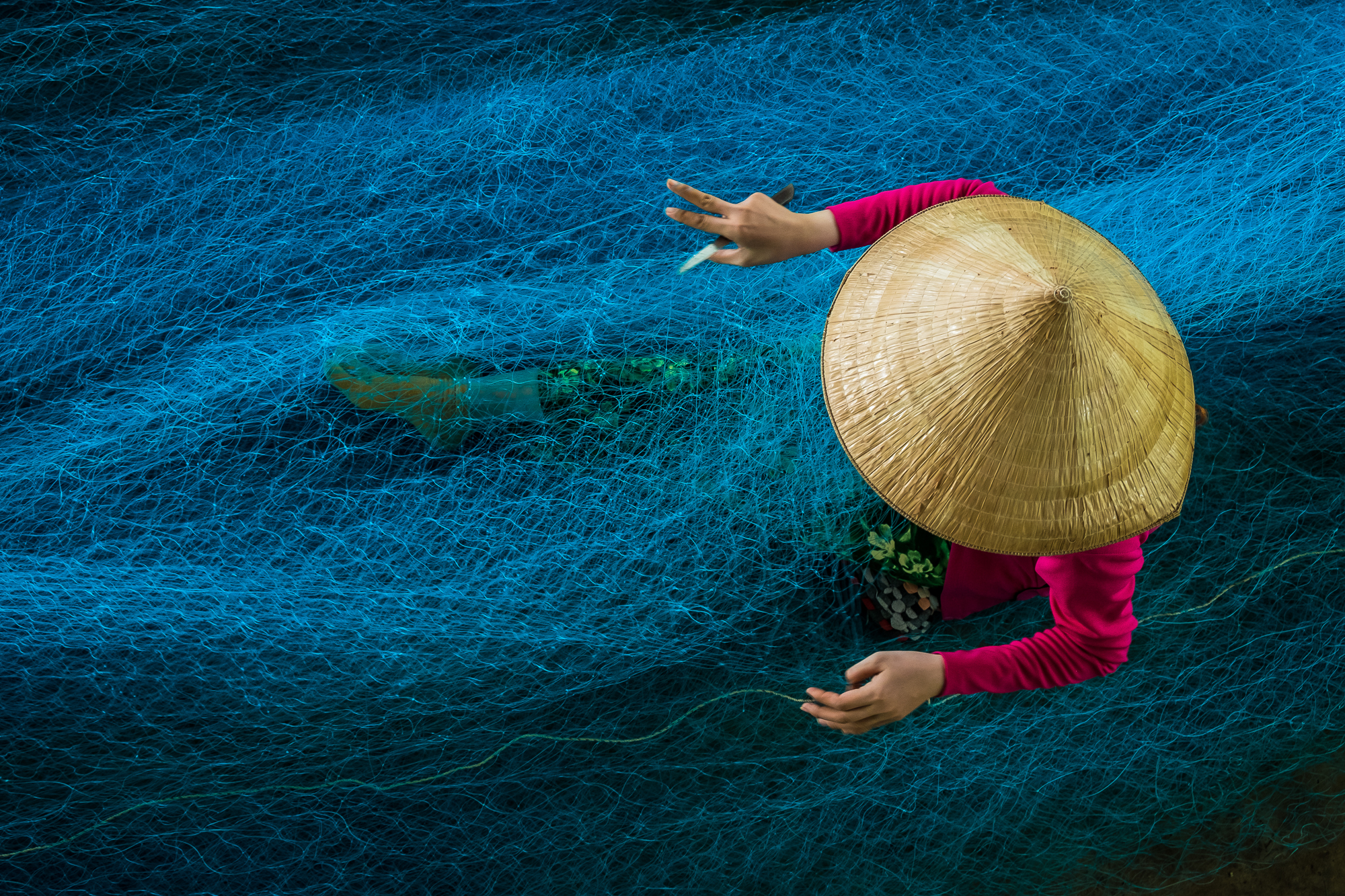 A lady is seen as she is busy in repairing the nets in a workshop situated in the outskirts of Bac Lieu, Vietnam