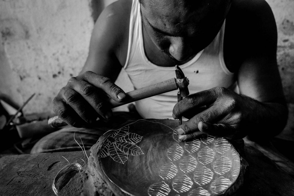 Meticulous and precision work for engraving the silver into the Bidriware