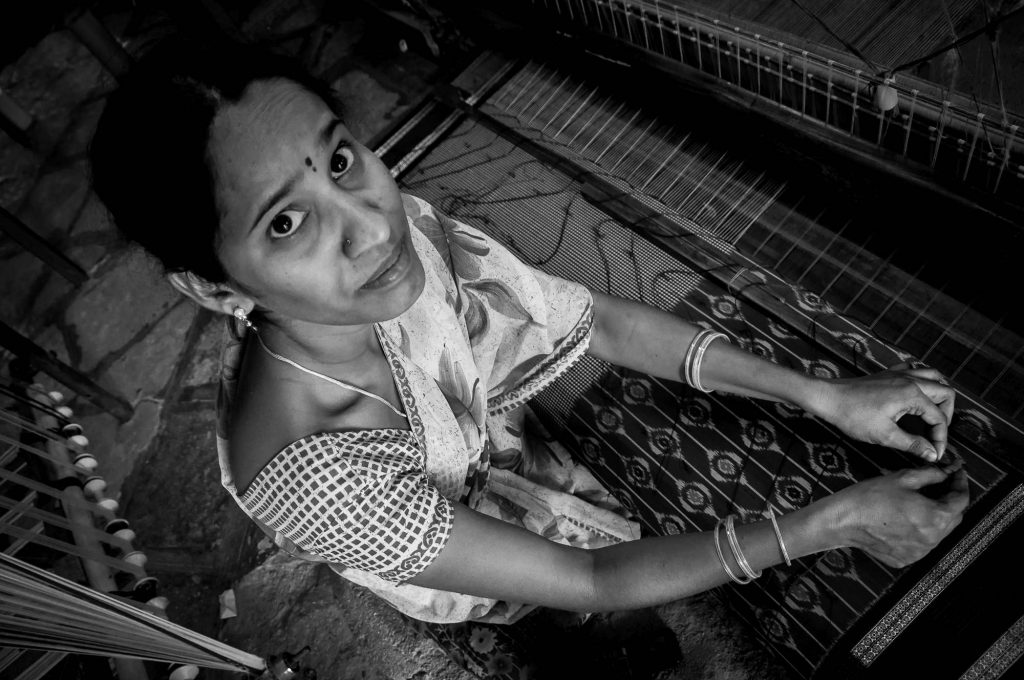 A lady poses as she works in the weaving factory