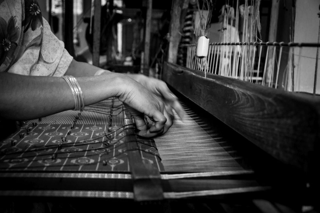 Hands of a lady are seen as she aligns the yarns to create design patterns in the saree