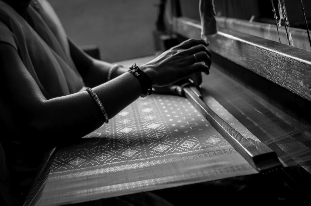 Hands are seen as a lady weaves sarees in a workshop at Pochampally
