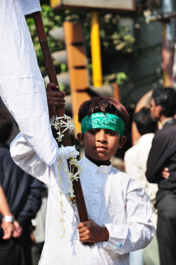 A kid carrying a white flag, the symbol of peace, in his hand.