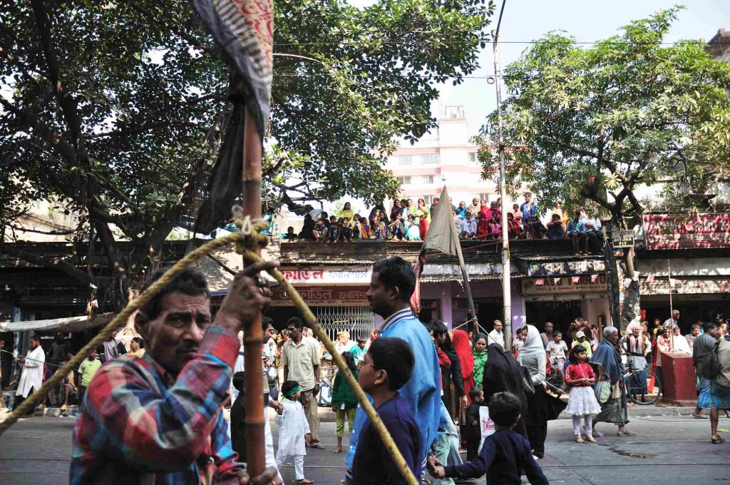 Hundreds of spectators from all religions watching the parade as it passes through the streets of Central Kolkata.