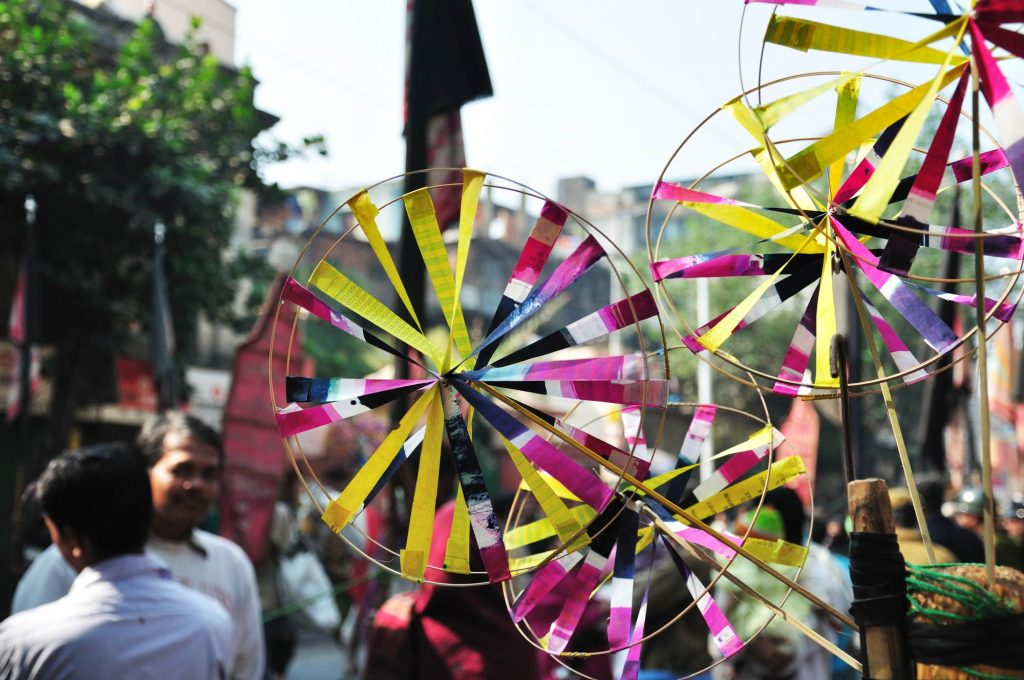 A vendor selling paper-windmills as the parade passes by.