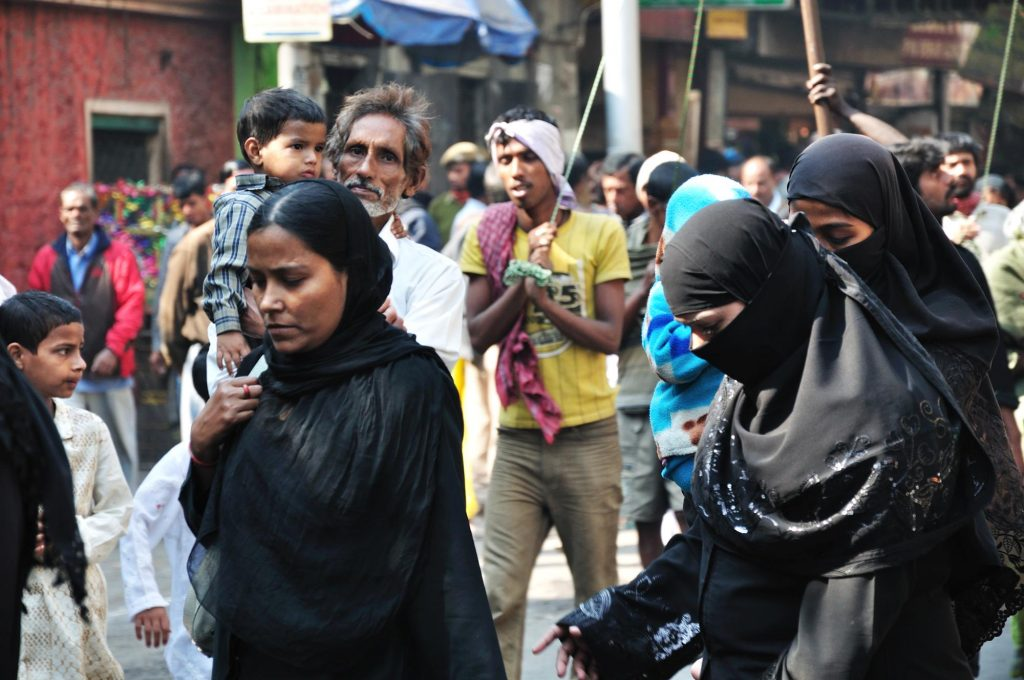 Muslim women wearing black borkhas taking part in the procession. The color black is regarded as the color of mourning.