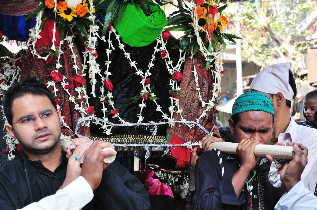 Muslim men carrying a sacred mausoleum, decorated with cloths and flowers, on their shoulders in the procession.