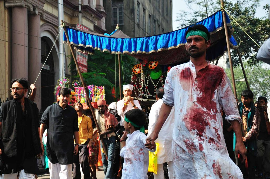 A Muslim man and his son wearing white dresses soaked with blood walking in the parade.