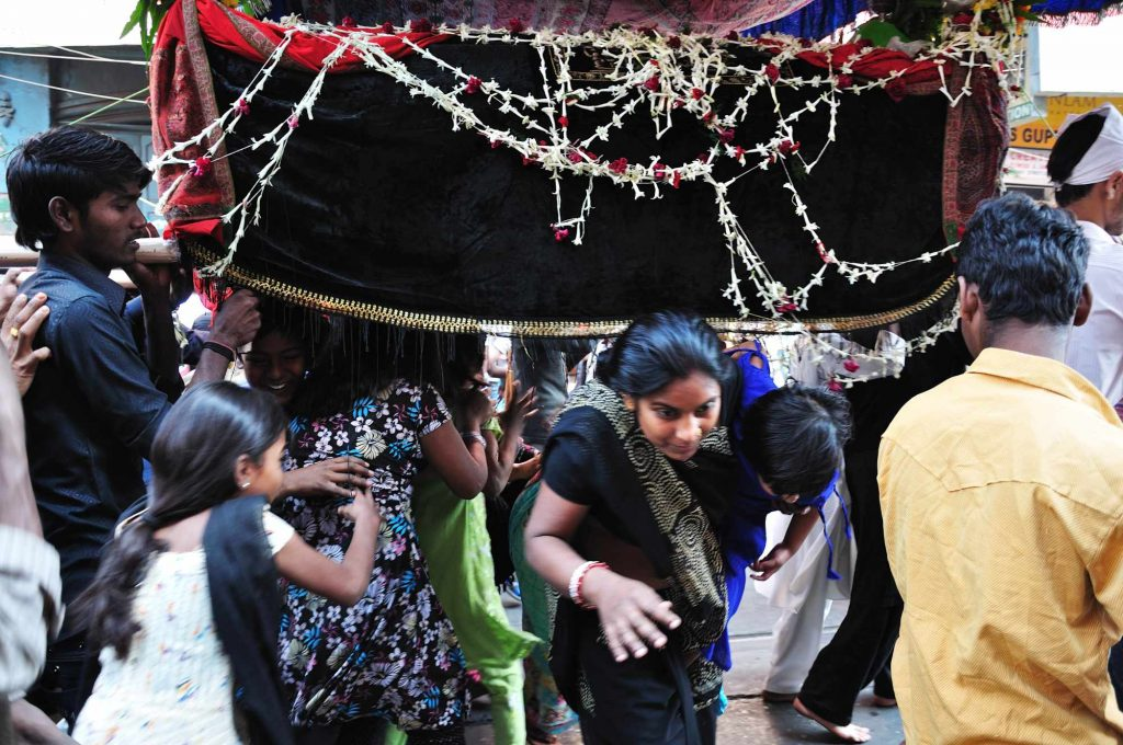 Girls and women from other religions crossing underneath a holy mausoleum being carried in the procession. This act is believed to bring fortune and good luck.