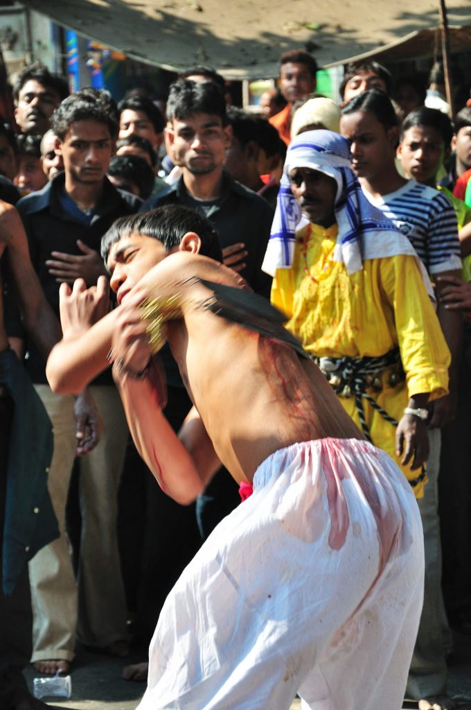 A young Muslim boy hitting himself with a bundle of sharp knives.