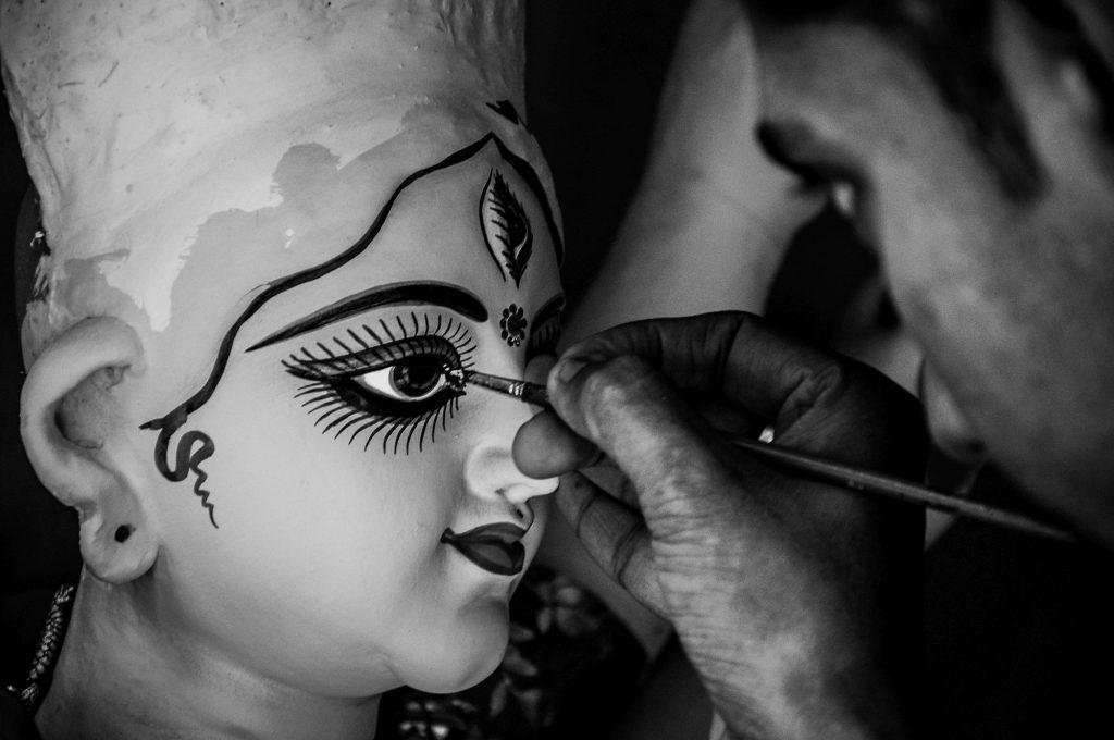An artisan paints the eye of the Goddess