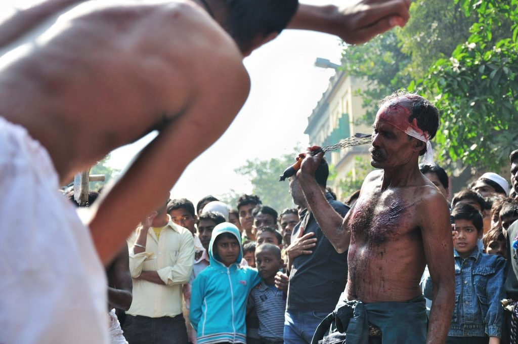 A Muslim devotee, already wounded, hitting his back and head with sharp knives in public.