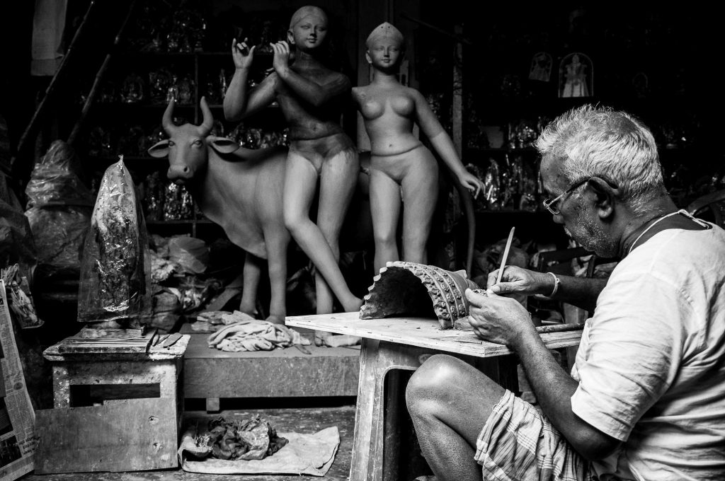 An artisan carves out the intricate details on the idols