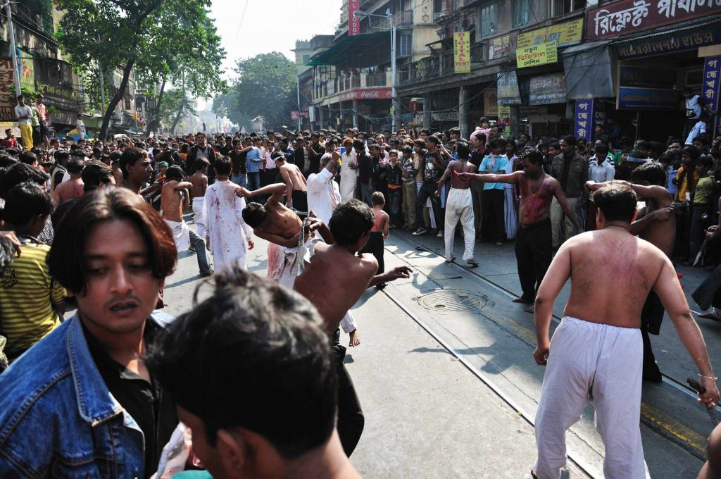 The mournful act of the Muslim devotees being watched by the crowd. The mourners walk barefoot on the road and hit themselves with sharp knives or blades.