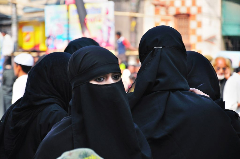 Muslim women watching the mournful event. The sorrow, the pain, and the grief can be seen in their eyes too.