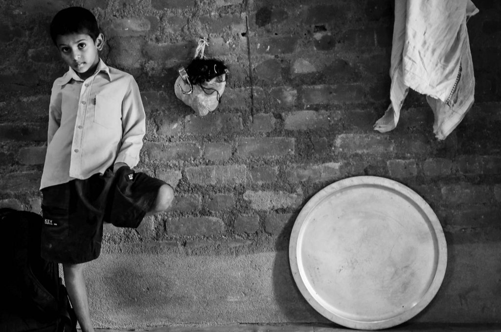 A kid poses against a wall in one of the workshops in Pochampally