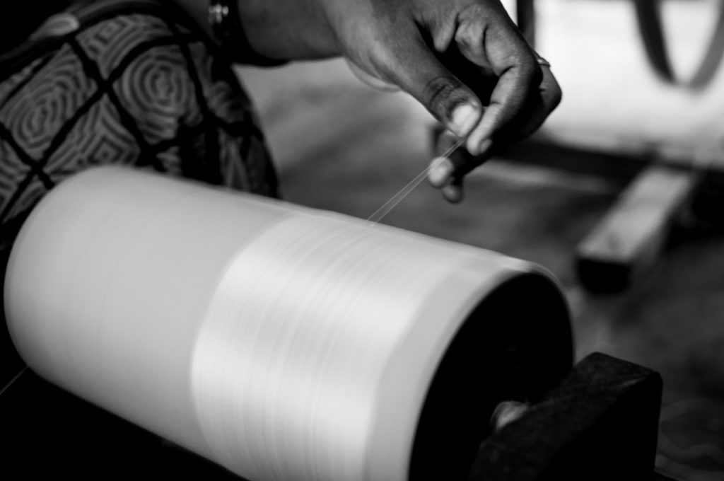 A lady winds the cotton yarn into a spool before those are used in the weaving machine