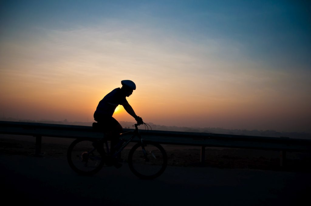 A cyclist is seen as the sun rises over the horizon.