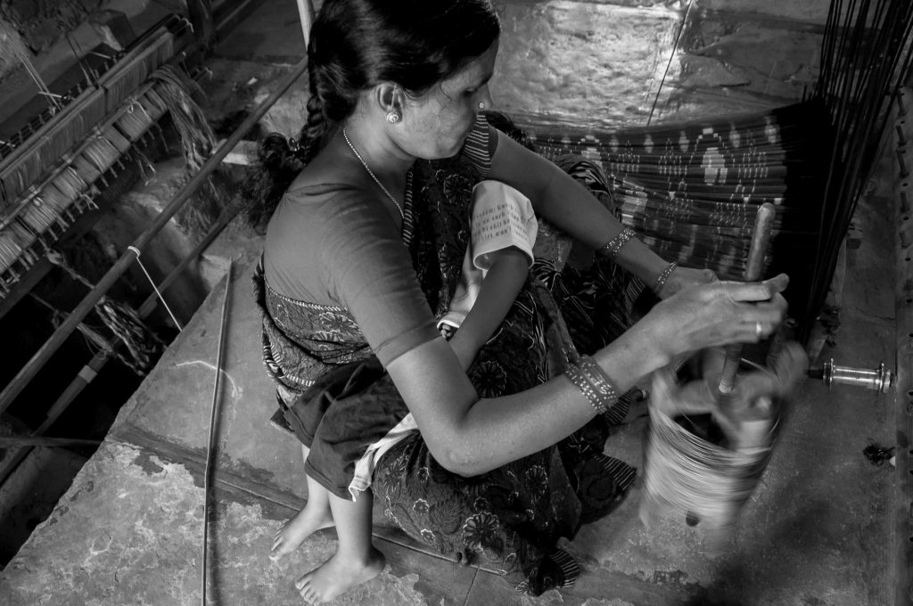 A lady winds the yarn as her son sleeps in her lap