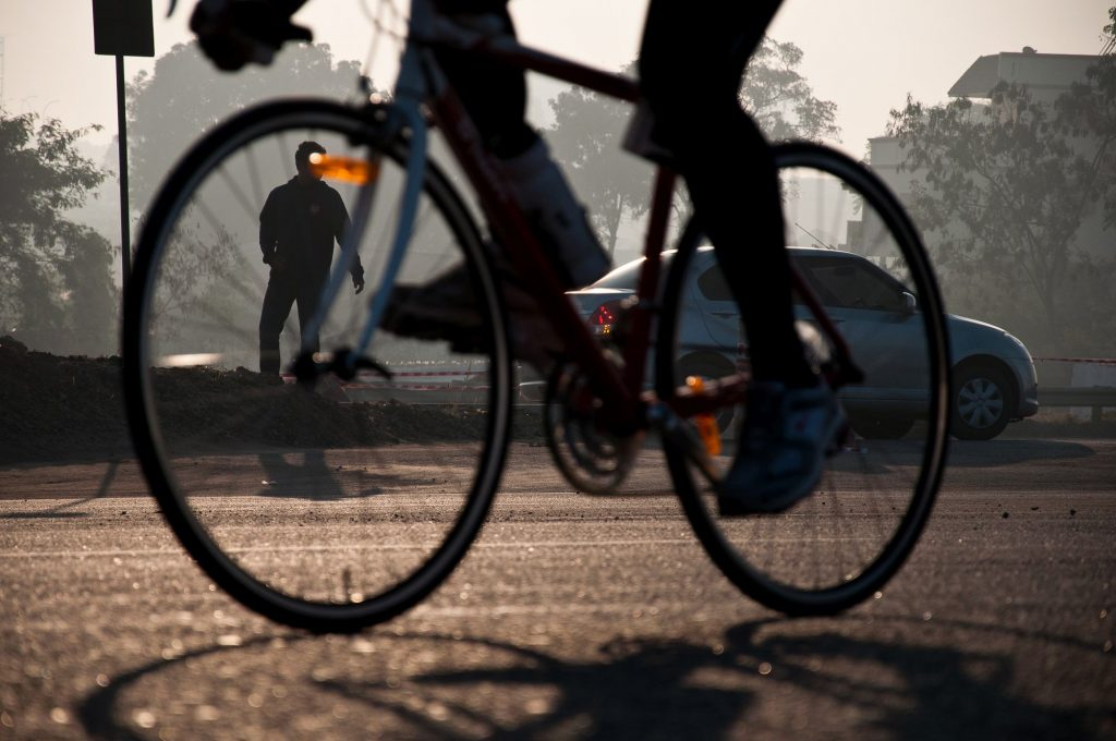 A person waiting to cross the road as the bicycles pass by.