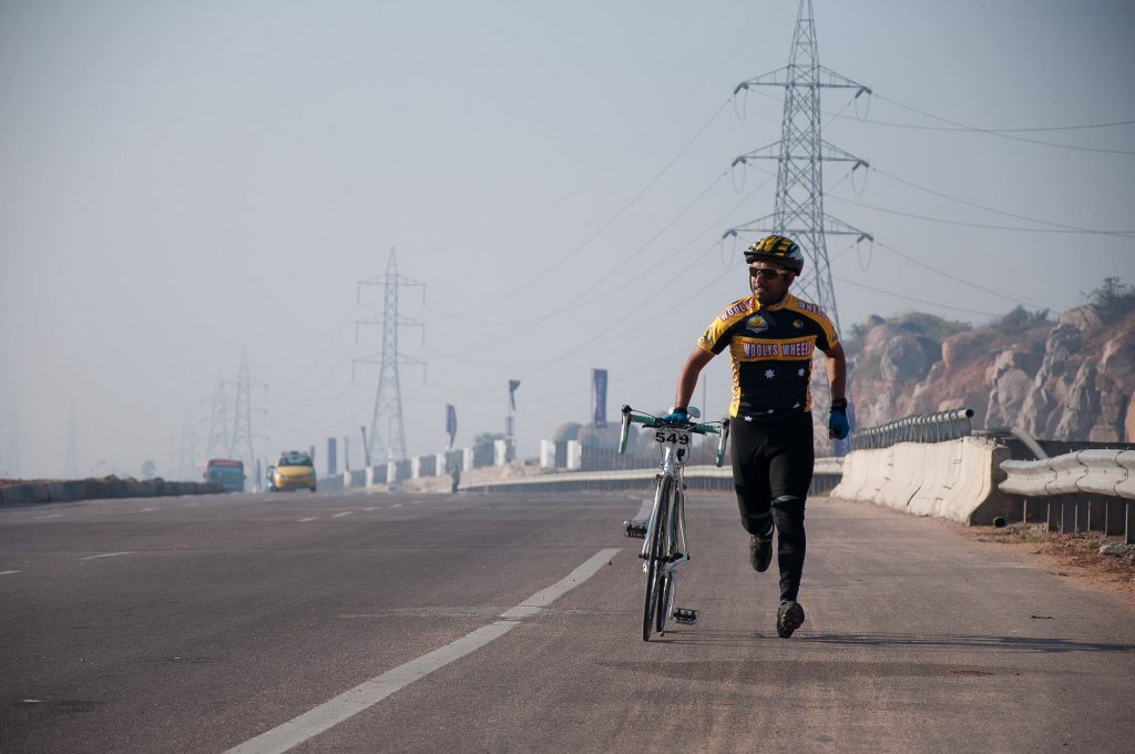 A rider sprints with his bicycle to finish the race due to the flat tire of his bicycle.