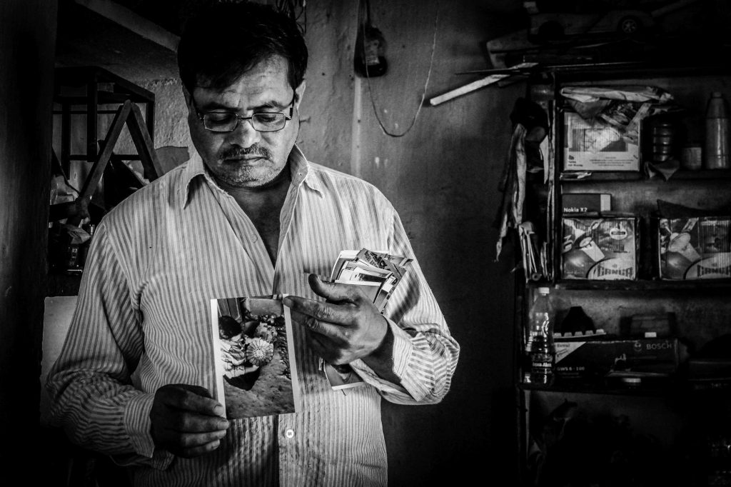 An artisan showing his photos while making the Bidriware