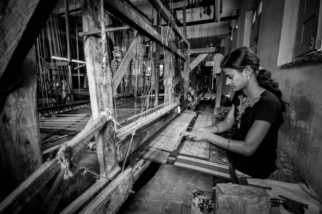 A worker is busy in weaving saree in the workshop