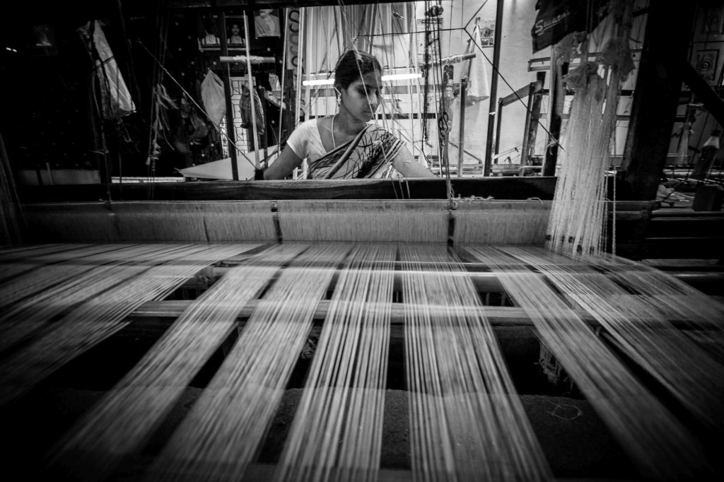 A lady weaving sarees in weaving machine