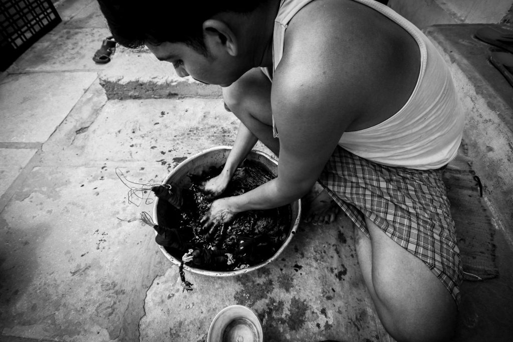 A man is seen as he dyes the cotton threads. These are the specific dyes uses in fabric industries