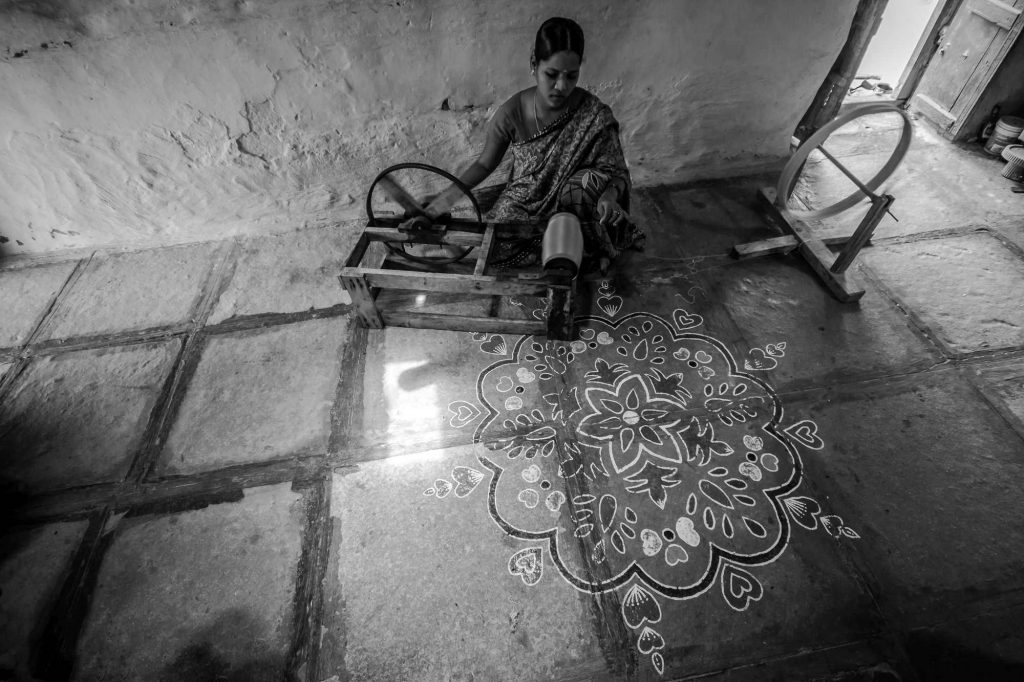 A lady is seen as she spools the yarn using a hand-spinning wheel