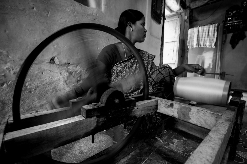 A lady spins the wheel to wind the yarn into spool