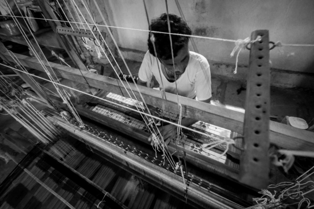 A man is seen as he continues to weave silk sarees
