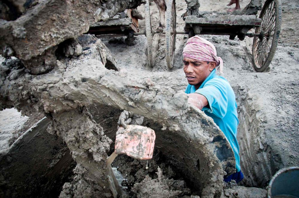 A worker add waters and grinds the mud to make the right consistency for molding into bricks