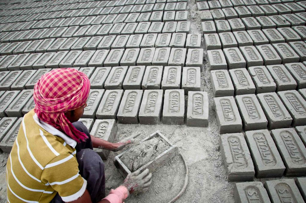 A worker molds the bricks and leave them for drying under the sun
