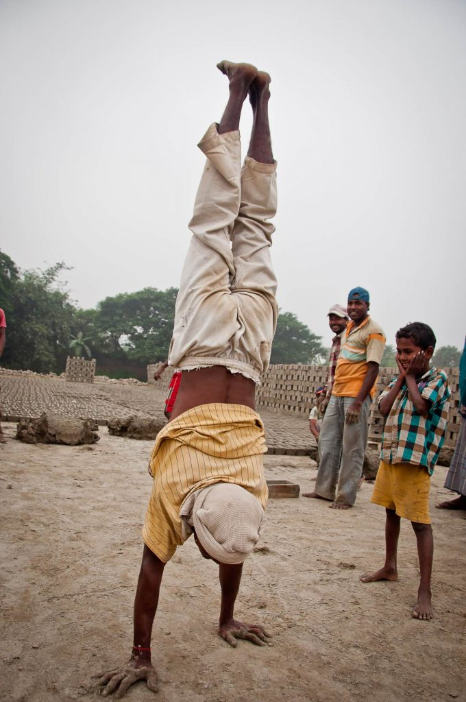 A worker shows his gymnastic skills as he takes a break from his work